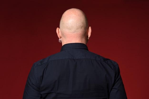 Portret łysy mężczyzna, widok z tyłu, na czerwonym tle