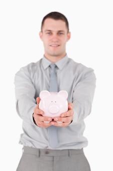 Portret młody biznesmen trzyma prosiątko banka