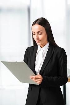 Portret młody bizneswoman patrzeje schowek