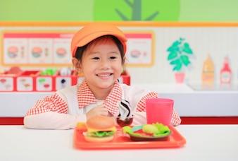 Portret mała Azjatycka dzieciak dziewczyna bawić się w fasta food sklepie.