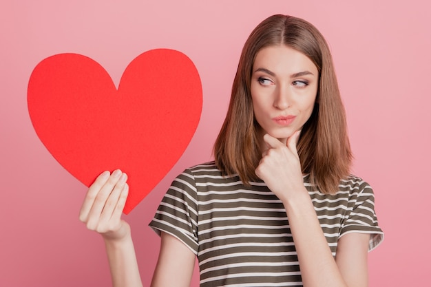 Portret mądrej wątpliwej damy trzyma czerwoną kartę serca palec podbródek myśli na różowym tle