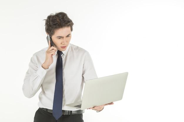 Portret mądrze młody azjatykci biznesmen jest ubranym białego koszulowego mienie i patrzeje komputerowy laptop i robi wezwaniu z mądrze telefonem komórkowym