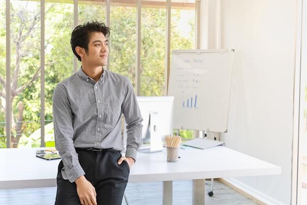 Portret mądrze młody azjatykci biznesmen w biurowym pokoju z komputerem i spotkanie deską z prętową mapą.