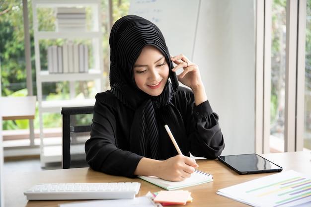 Portret mądrze piękny muzułmański bizneswoman pracuje w biurze