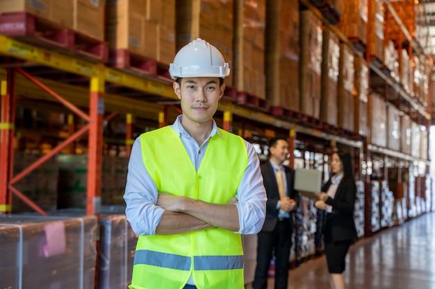 Portret magazynowy pracownik z ludźmi biznesu stoi w wielkim magazynie z krzyżować rękami.