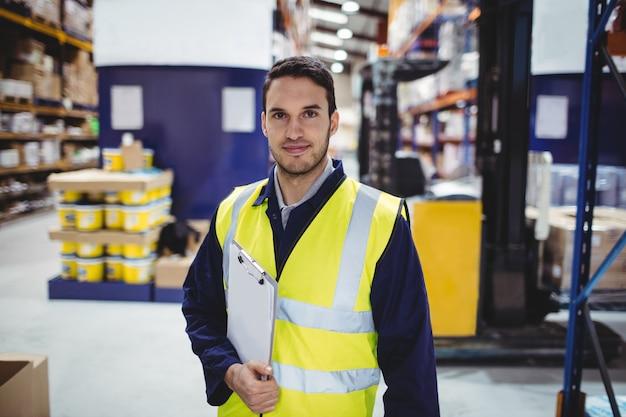 Portret magazynowy pracownik z schowkiem w magazynie