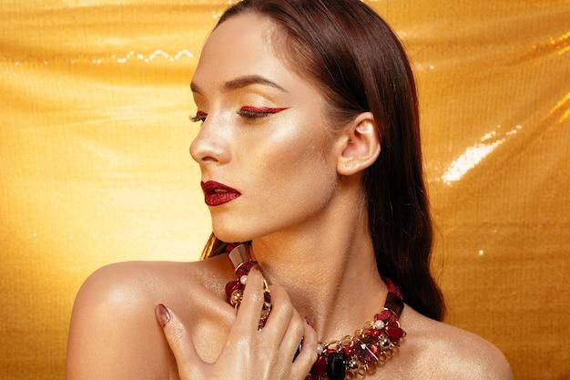 Portret magicznej dziewczyny w złotym złotym makijażu portret zbliżenie w kolorze strzału studio