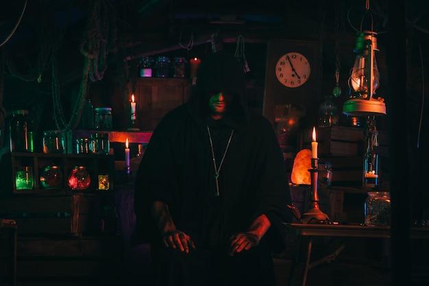 Portret magika alchemika we wnętrzu ciemnego warsztatu laboratoryjnego z kolbami i sprzętem. halloweenowy cosplay