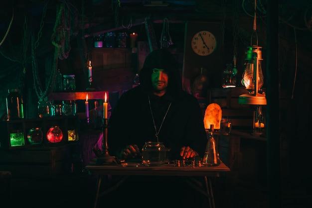 Portret magika alchemika we wnętrzu mrocznego warsztatu laboratoryjnego z kolbami i sprzętem