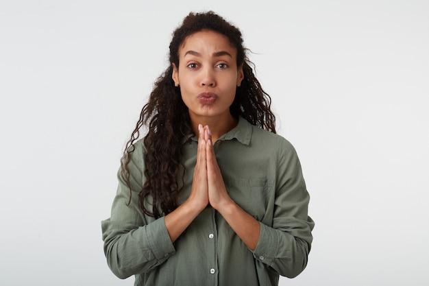 Portret mającej nadzieję brązowookiej, kręconej brunetki, ciemnoskórej kobiety z przypadkową fryzurą, trzymając uniesione dłonie razem i wydrążając usta, odizolowane na białym tle
