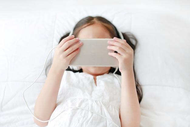 Portret mała azjatycka dziewczyna używa hełmofony słucha muzykę smartphone podczas gdy kłamający na łóżku w sypialni w domu.