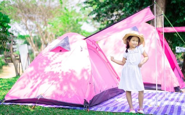 Portret mała azjatykcia dziewczyna jest ubranym kapeluszową pozycję z namiotami podczas gdy iść obozować