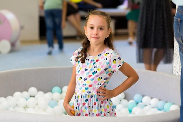 Portret mała dziewczynka bawić się w basenie z plastikowymi piłkami