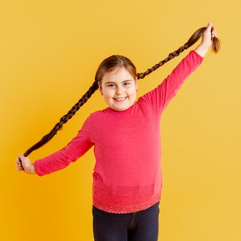 Portret mała dziewczynka bawić się z jej włosy