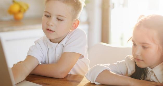 Portret mała dziewczynka i chłopiec używa cyfrową pastylkę