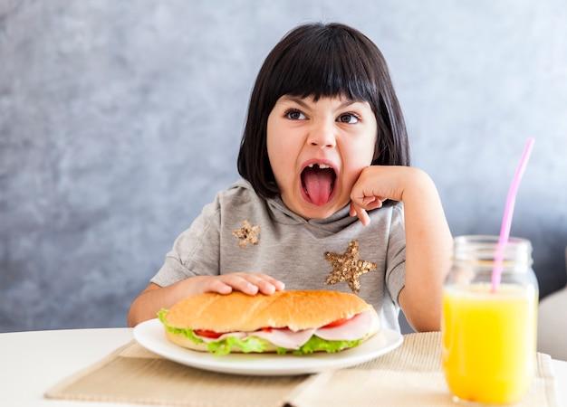 Portret mała dziewczynka ma śniadanie w domu