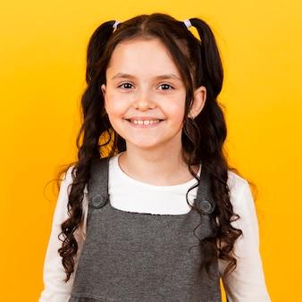 Portret mała dziewczynka ono uśmiecha się z warkoczami włosianymi