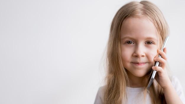 Portret mała dziewczynka opowiada nad telefonem