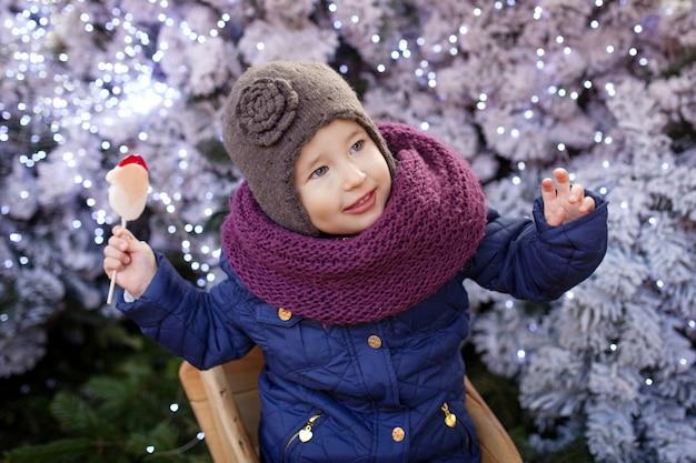 Portret mała dziewczynka przy bożenarodzeniowym czasem plenerowym.