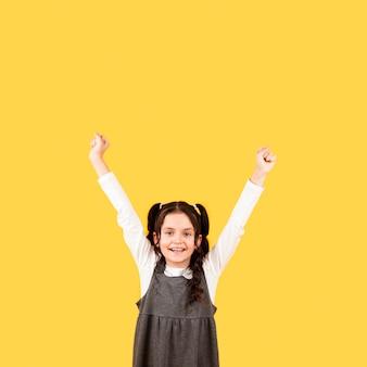Portret mała dziewczynka szczęśliwa z ręką uniesioną do góry