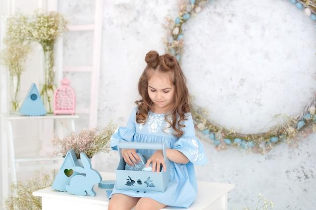 Portret mała dziewczynka w błękit sukni obsiadaniu przy stołem w kuchni z wielkanocnymi jajkami w koszu. wielkanocne wnętrze. wiosenna dekoracja domu. szczęśliwa rodzina przygotowuje się do wielkanocy. dzieci świętują wielkanoc.