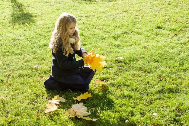 Portret mała dziewczynka z żółtymi liśćmi klonowymi