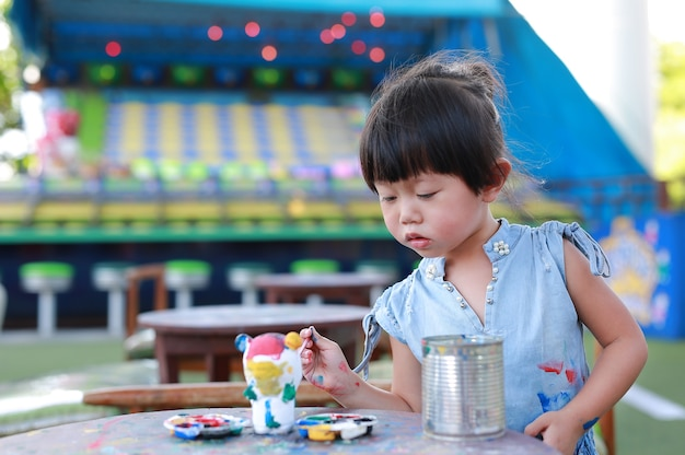 Portret mała dziewczynka zamierza malować na sztukateryjnej lalce