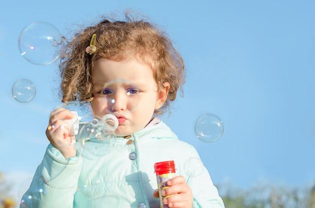 Portret mała śliczna dziewczyna dmucha mydlanych bąble. szczęśliwe dziecko bawi się na zewnątrz. dziecko bawi się na łonie natury. nieostrość. kopia przestrzeń