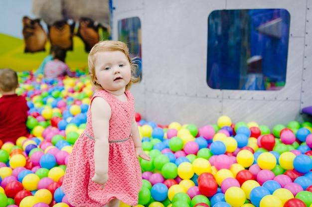Portret mała śliczna dziewczynka księżniczka niemowlę 1-2 lata stojące i bawiące się balonami, kolorowe kulki na placu zabaw, basen z piłeczkami, suchy basen na przyjęcie urodzinowe. koncepcja obchodów pierwszego roku.