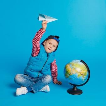 Portret mała śmieszna chłopiec z nakrętki i zabawki papieru samolotem