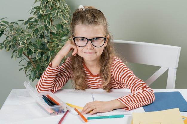 Portret mała uśmiechnięta dziewczyna siedzi przy biurkiem w szkłach