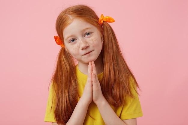 Portret mała żałosna rudowłosa dziewczynka z dwoma ogonami, patrzy w kamerę i złożone dłonie, gest drapieżnika, nosi żółtą koszulkę, stoi na różowym tle.