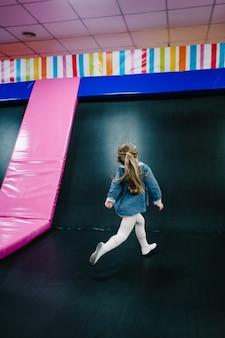 Portret małe dziecko, dziewczynka księżniczka 3-4 lata bawiące się i skaczące na trampolinie w pokoju zabaw dla dzieci, centrum sportowe kryty plac zabaw na przyjęcie urodzinowe. koncepcja uroczystości wakacje, rozrywka.