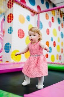 Portret małe słodkie dziecko dziewczynka księżniczka niemowlę 1-2 lata gry i skoki na trampolinie w pokoju zabaw dla dzieci, kryty na przyjęcie urodzinowe. koncepcja uroczystości wakacje, imprezy, rozrywka.