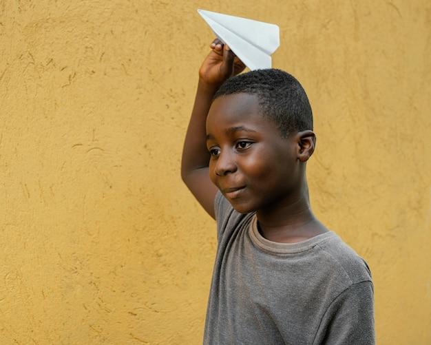 Portret małego afrykańskiego chłopca bawiącego się samolotem