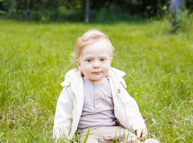 Portret małego białego chłopca kaukaski. w letni dzień na trawie w parku siedzi dziecko.