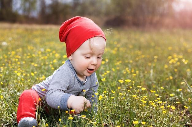 Portret małego białego chłopca rasy kaukaskiej w czerwonym kapeluszu. dziecko siedzi na trawie w parku w letni dzień.