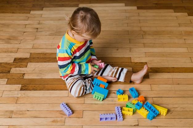 Portret małego chłopca bawi się zabawkami