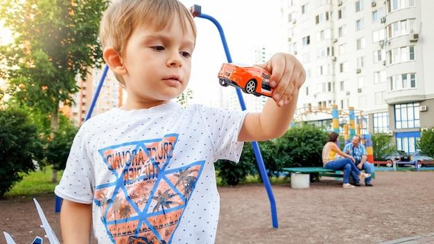 Portret małego chłopca bawiącego się samochodzikami na placu zabaw