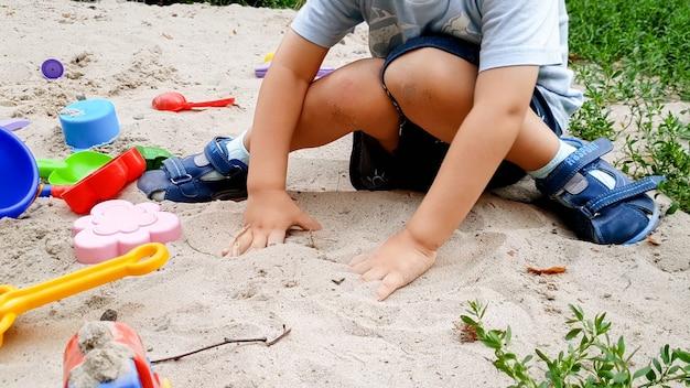Portret małego chłopca bawiącego się zabawkami i kopiącego piasek w piaskownicy w parku