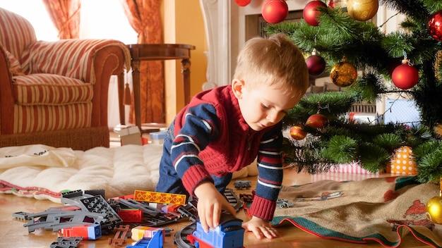 Portret małego chłopca bawiącego się zabawkowym pociągiem i kolejkami na podłodze pod choinką