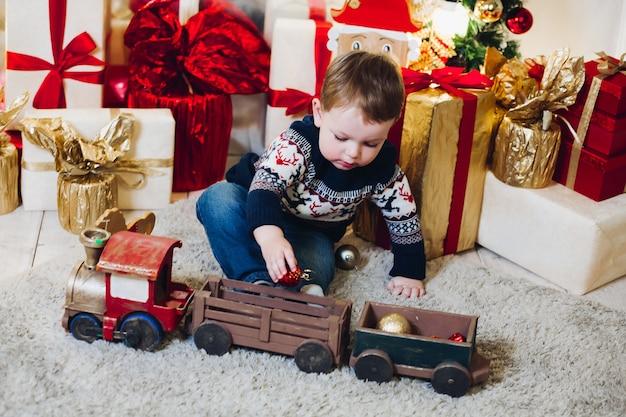 Portret małego chłopca blondynka siedzi na podłodze w urządzonym studio i bawi się prezentami świątecznymi i pudełkami