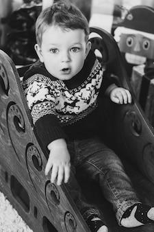 Portret małego chłopca blondynka siedzi na sankach
