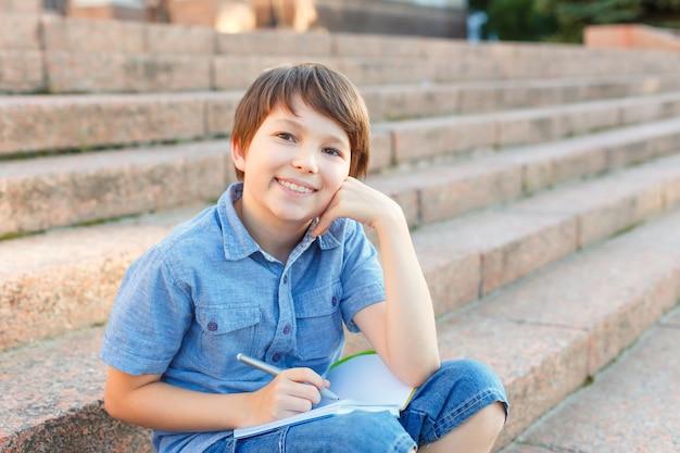 Portret małego chłopca. dziecko pisze w zeszycie ołówkiem.