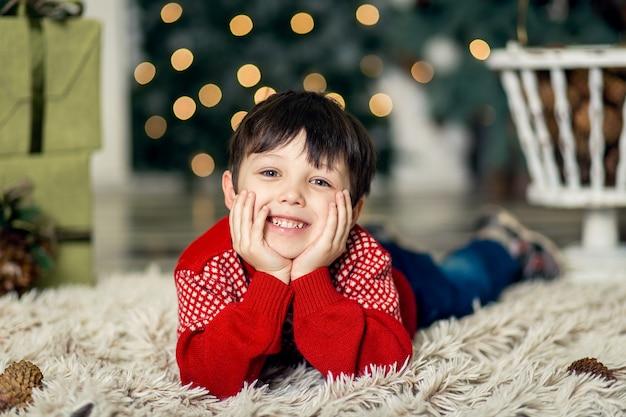 Portret małego chłopca grać z szyszek sosny w pobliżu choinki. ozdoby świąteczne. wesołych świąt i szczęśliwego nowego roku 2020