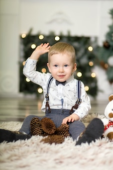 Portret małego chłopca grać z szyszek sosny w pobliżu choinki
