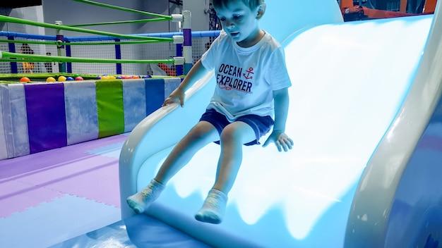 Portret małego chłopca jadącego na kolorowej oświetlonej zjeżdżalni na placu zabaw w parku rozrywki