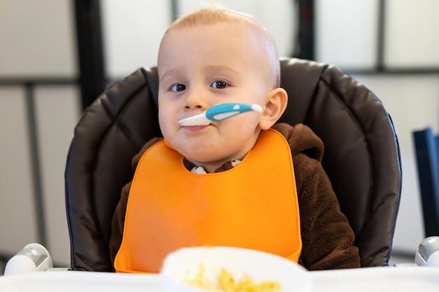 Portret małego chłopca, jedzenie się na krześle i patrząc w kamerę.