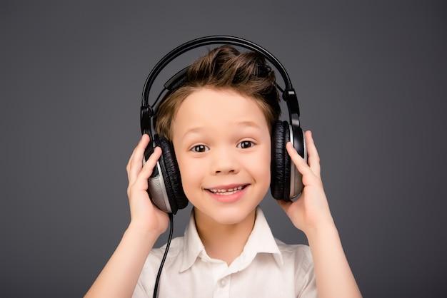 Portret małego chłopca ładny słuchanie muzyki w słuchawkach