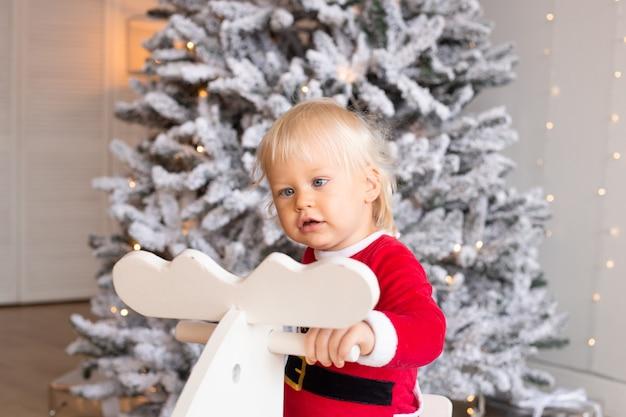 Portret małego chłopca na koniu na biegunach w pobliżu choinki w świątecznie udekorowanym domu